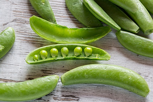 Whole and opened peasecods of snow peas on wood