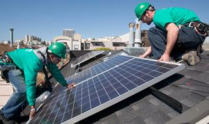Micah Fromkin, right, crew leader for Solar City solar panel installers and Christian Lee, a junior installer, carefully place a solar panel onto the roof of a residential building in San Francisco, Wednesday, March 11, 2009. (D. Ross Cameron/Staff Archives)