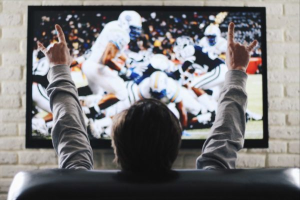 The man watches on sports the channel on TV the American football