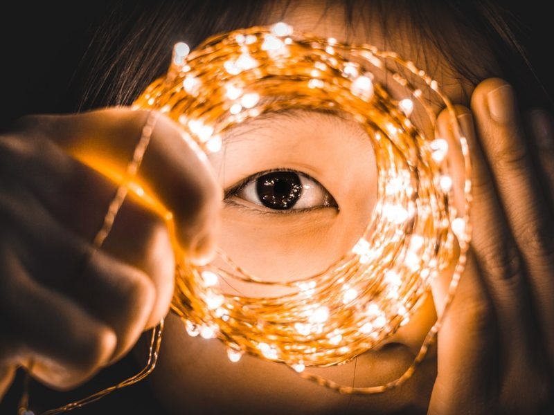 Woman's eye looking through ring of lights
