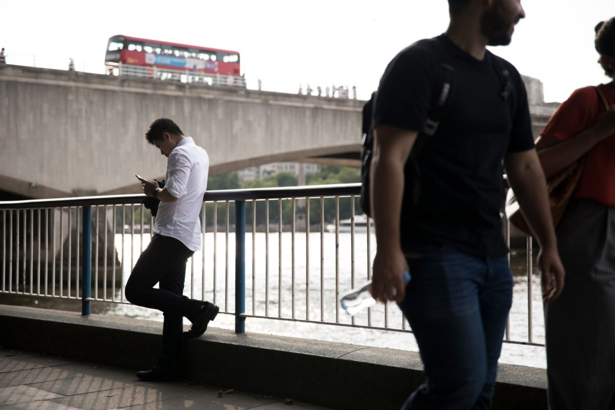 A man leaning against a fence along the Thames River looking at mobile phone