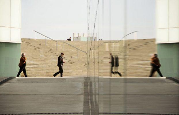 People walking toward mirror