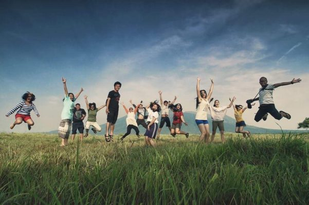 People jumping for joy in grass field