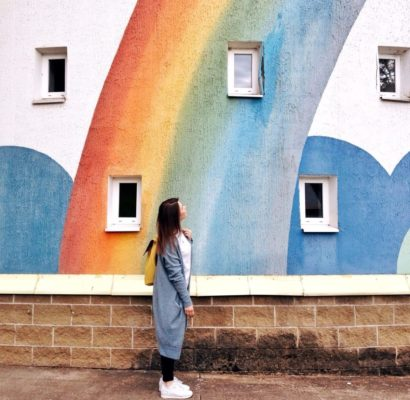 womwoman looking up at rainbow wall