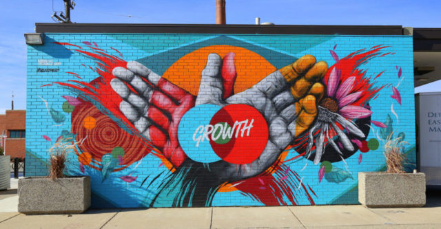 "Painting on brick wall depicting hands and word ""growth"""