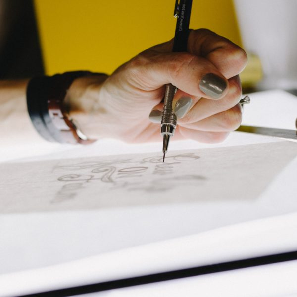 Woman drawing a design on paper with ink pen