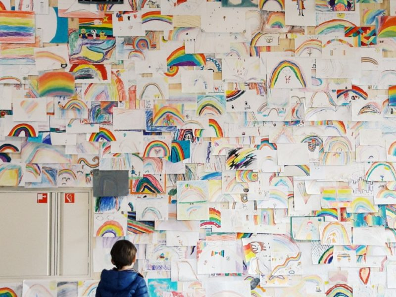 kid-in-colourful-clothes-watching-other-children-drawings-of-a-rainbow