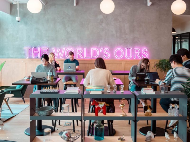 """The World's Ours"" people in co-working space on laptops"