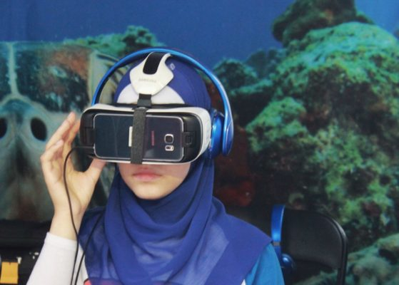 Young woman in a hijab using VR googles
