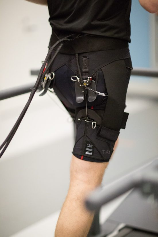 Picture of a man running with the assistance of a soft exosuit developed by The Wyss Institute at Harvard