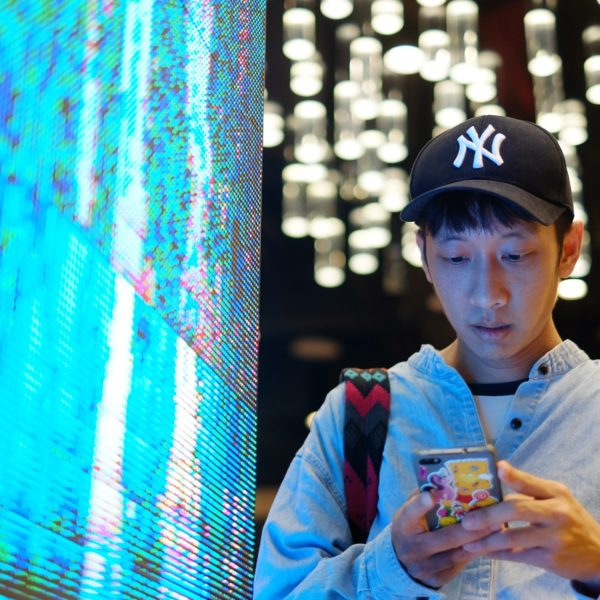 Young man using smartphone at the neon LED light screen