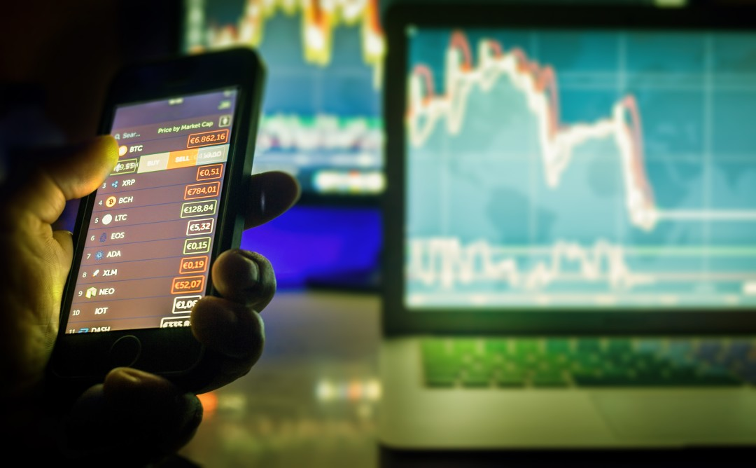 daytrader-in-dark-using-mobile-phone-and-screens-with-charts