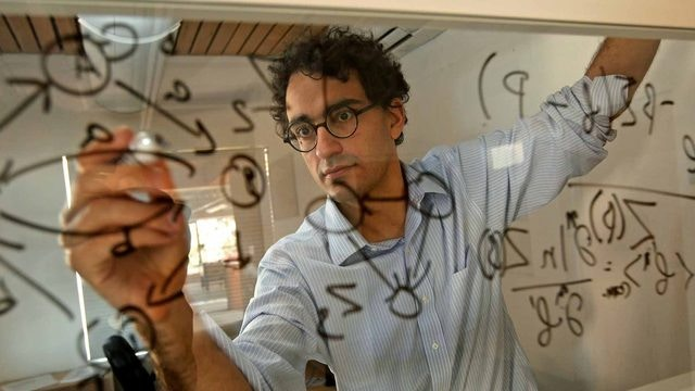 Simon Dedeo writing on board
