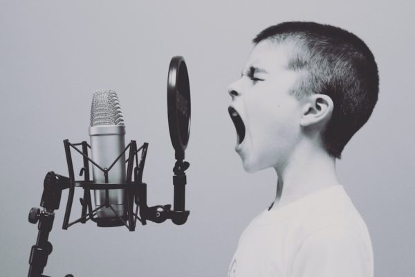 Little boy yelling into microphone